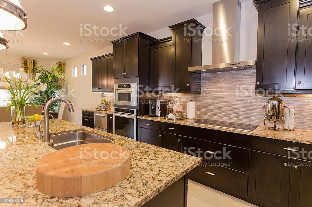 Luxury kitchen with dark cabinets and stainless steel appliances stock photo