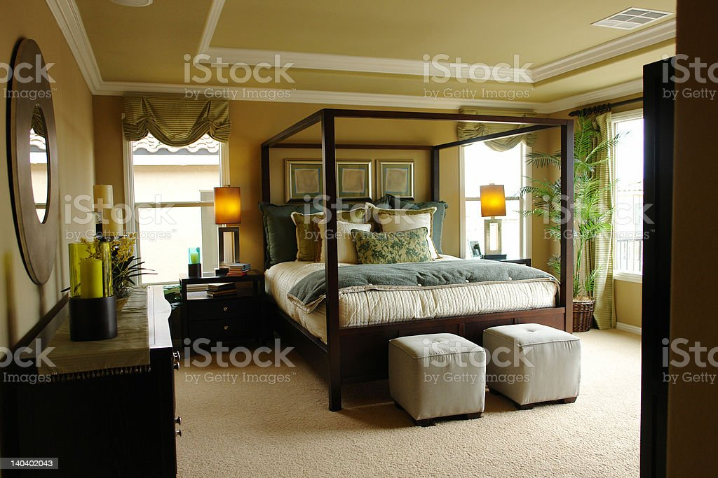 A luxury master bedroom with plenty of natural light stock photo