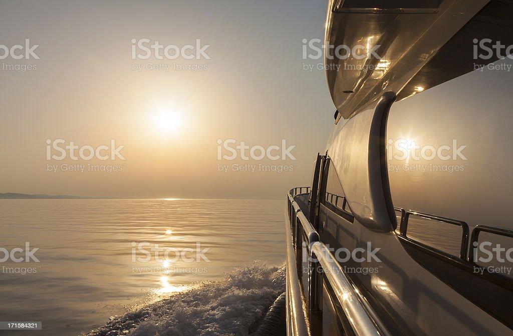 Luxury motor yacht sailing at sunset stock photo