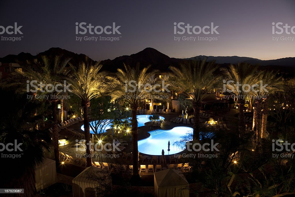 Luxury Resort Pools At Night With Palm Trees, Sunset, Mountains royalty-free stock photo