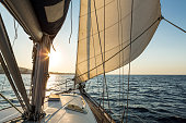 Luxury sailboat cruising at sea at sunrise