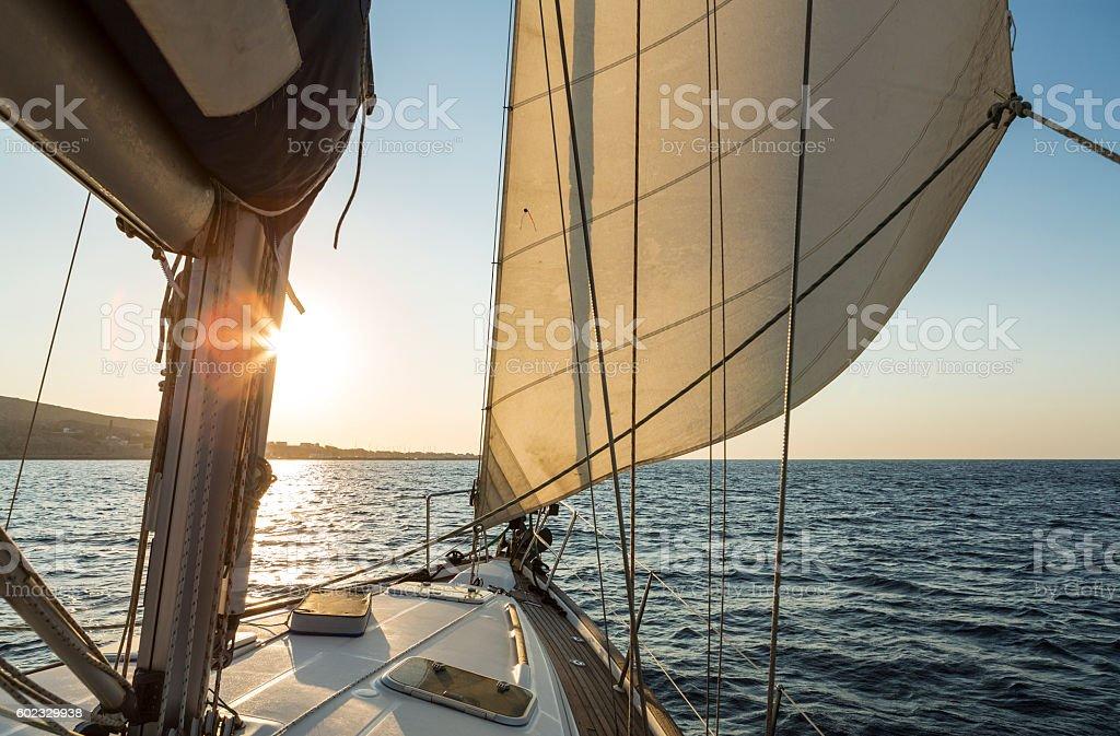 Luxury sailboat cruising at sea with morning sunrise ahead stock photo