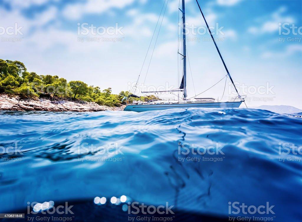 Luxury sailboat near tropical island stock photo
