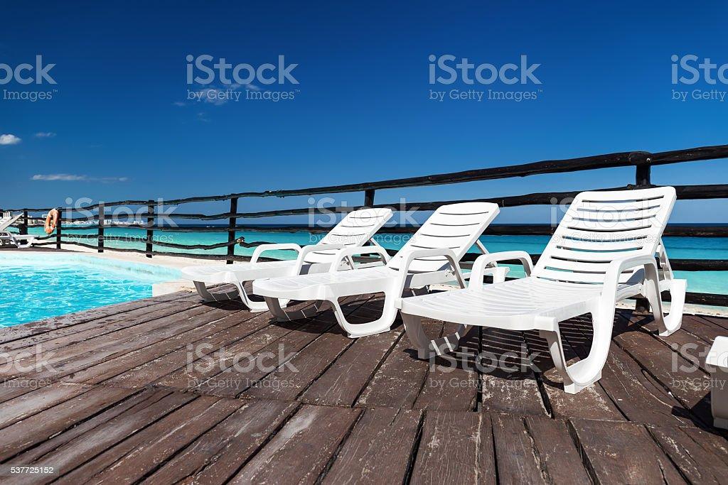 Luxury sunbeds on wooden floor near swimming pool stock photo