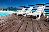 Luxury sunbeds on wooden floor near swimming pool
