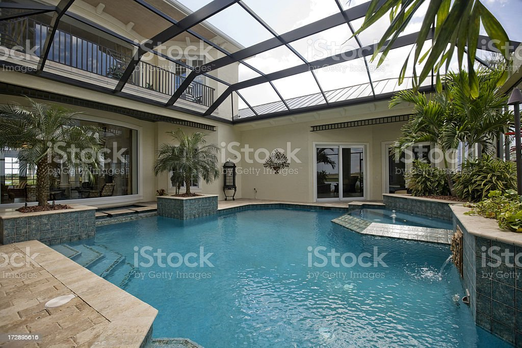 Luxury swimming pool with screen covered cage stock photo for Pool lanai cost