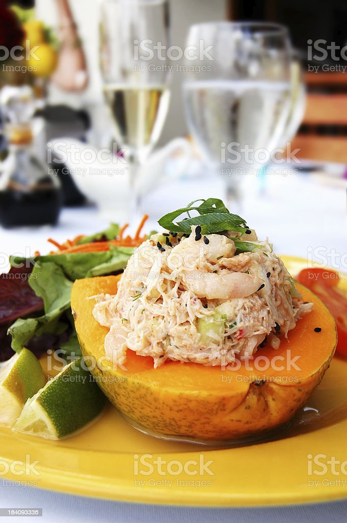Luxury Tropical Lunch: Lobster and Crab Meat Salad Stuffed Papaya stock photo