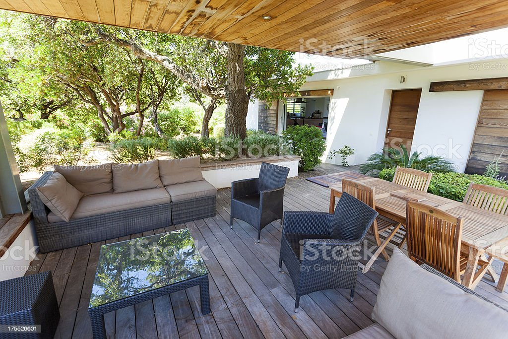\'Luxury modern villa with patio, furniture and green garden\'