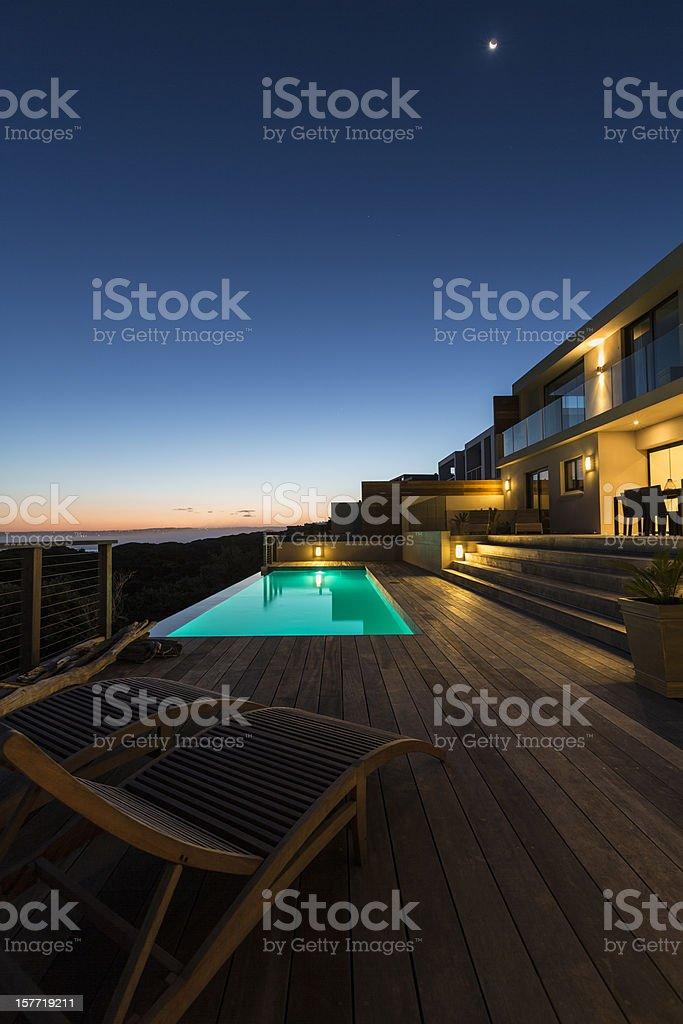 Luxury villa pool deck at dusk stock photo