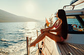 luxury woman yachting in sea at sunset