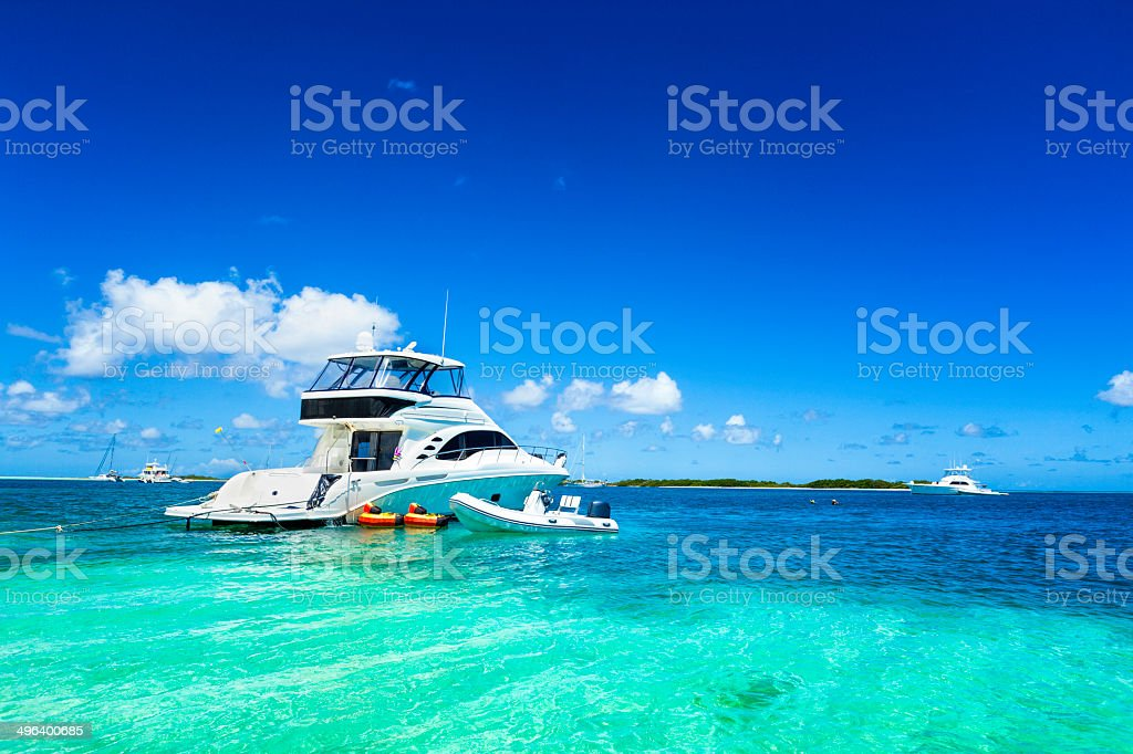 Luxury yacht anchored in a Tropical island turquoise beach stock photo