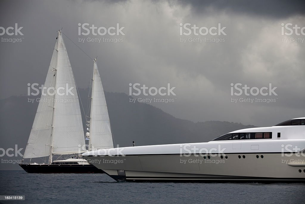 Luxury yacht and sailboats before a cloudy sky stock photo
