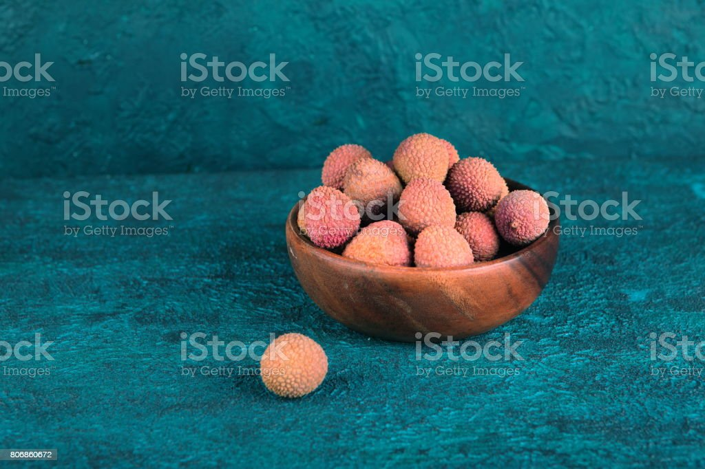 Lychee in a wooden bowl on a blue cement background stock photo