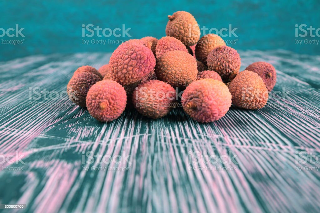 Lychee on a black and pink wooden background stock photo