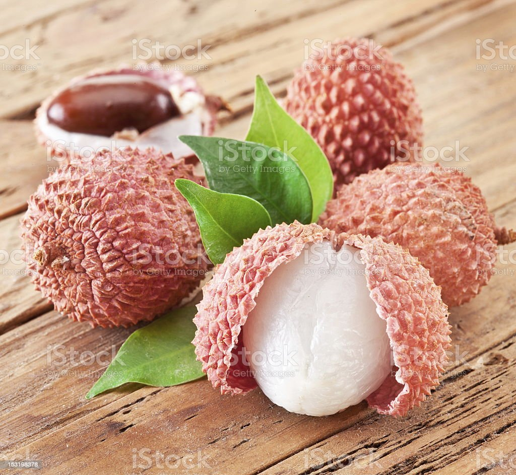 Lychee with leaves on a wooden table. stock photo