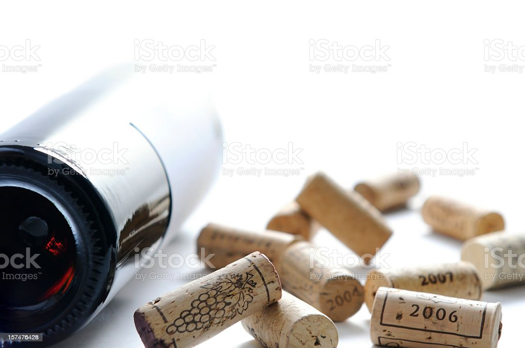 Lying bottle of red wine and scattered wine cork stoppers royalty-free stock photo