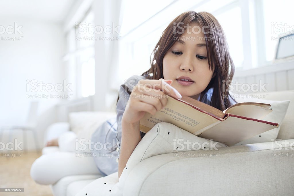 lying on couch and reading royalty-free stock photo