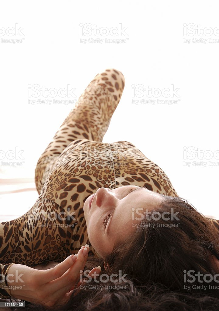 Lying woman in the dappled catsuit royalty-free stock photo