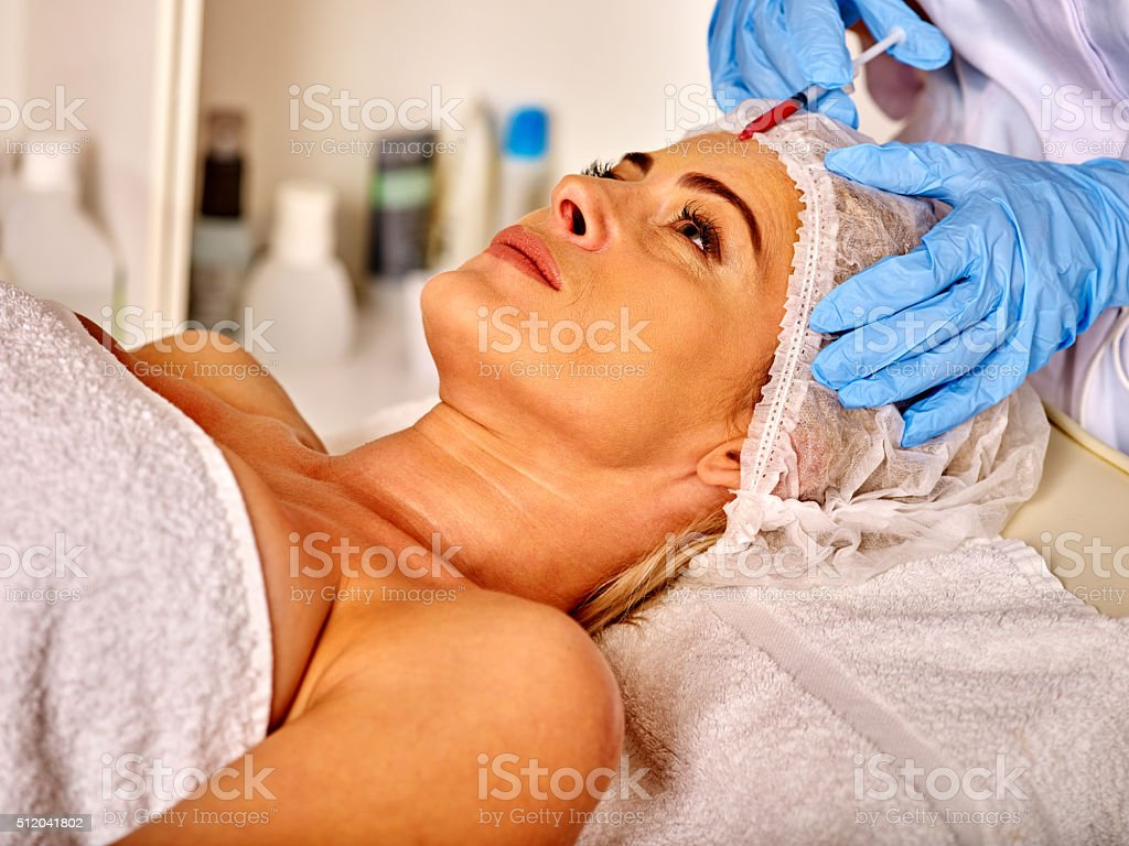 Lying woman middle-aged in spa salon with beautician. Woman stock photo