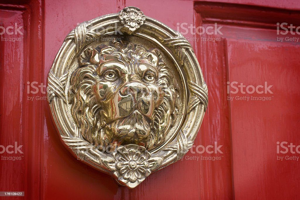 Lyon head door knocker on a red background royalty-free stock photo