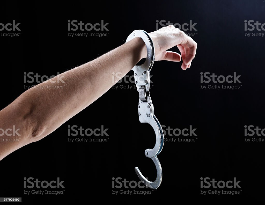 I'm free! Female hand wearing single, open handcuff. stock photo