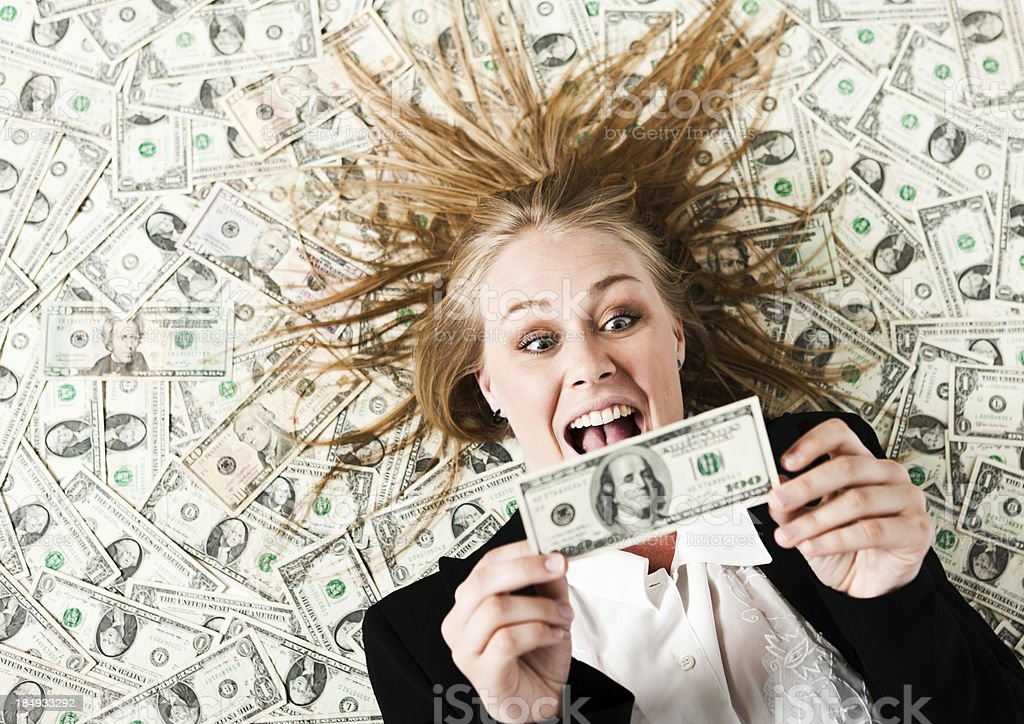 I'm rich! Pretty blonde on bed of dollars is delighted stock photo
