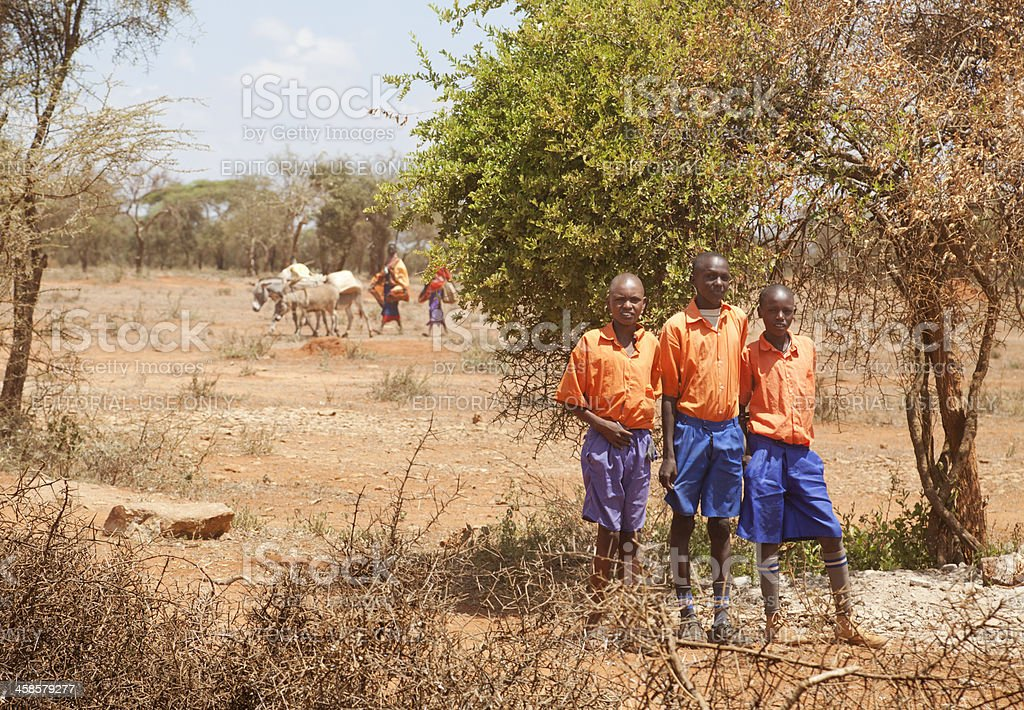 Maasai boys with school uniform, cattle and women in background. stock photo