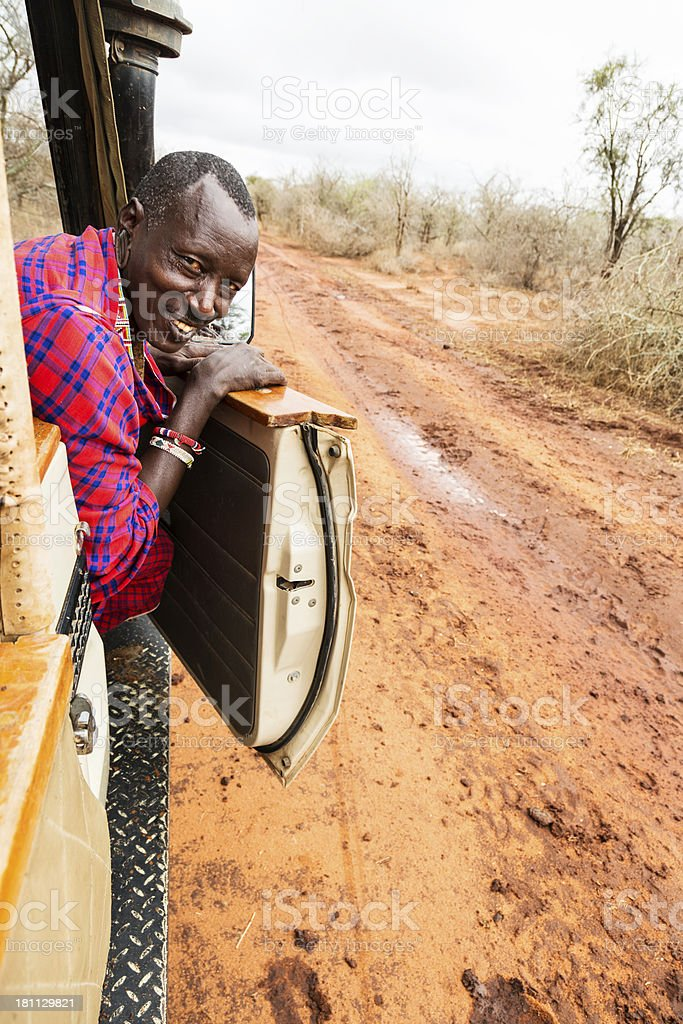 Maasai driver checking road in rainy season. stock photo