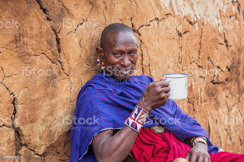 Maasai elder outside dung hut with a cup of tea. stock photo