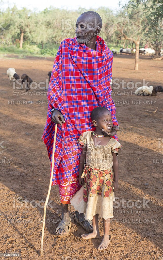 Maasai elder with daughter in village with goats. stock photo