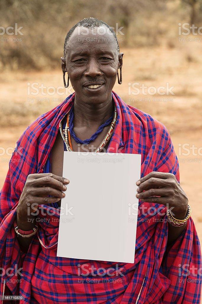 Maasai man with blank sheet of paper. Copyspace. stock photo