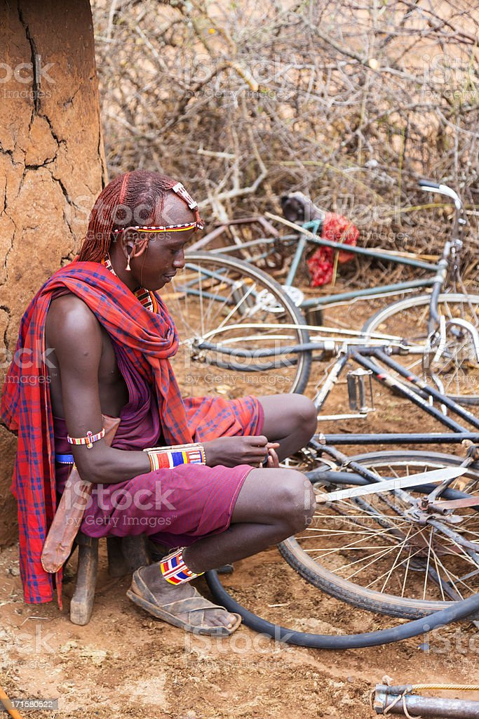 Maasai moran (young warrior) repairing puncture on his bicycle. royalty-free stock photo
