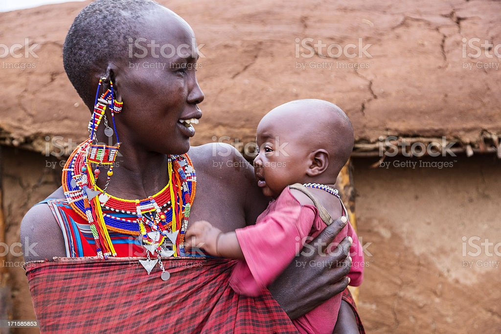 Maasai mother and child outside dung hut. stock photo