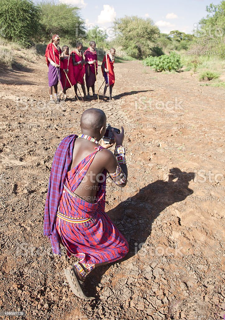 Maasai taking pictures of his friends in strong sunlight stock photo