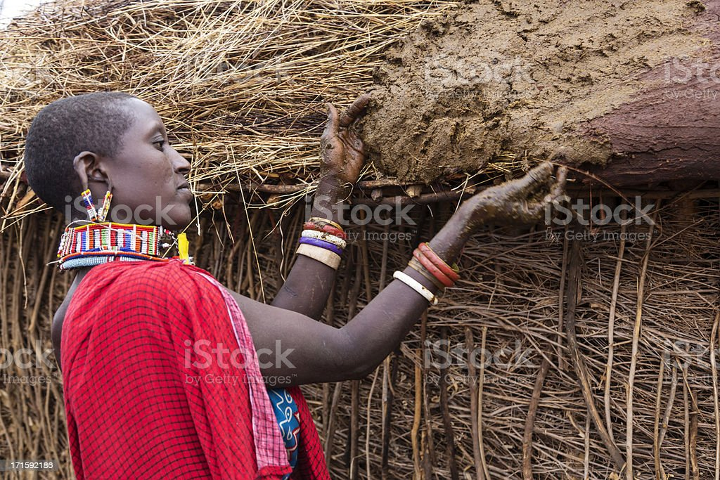 Maasai woman building hut. Putting cow's dung on roof. stock photo