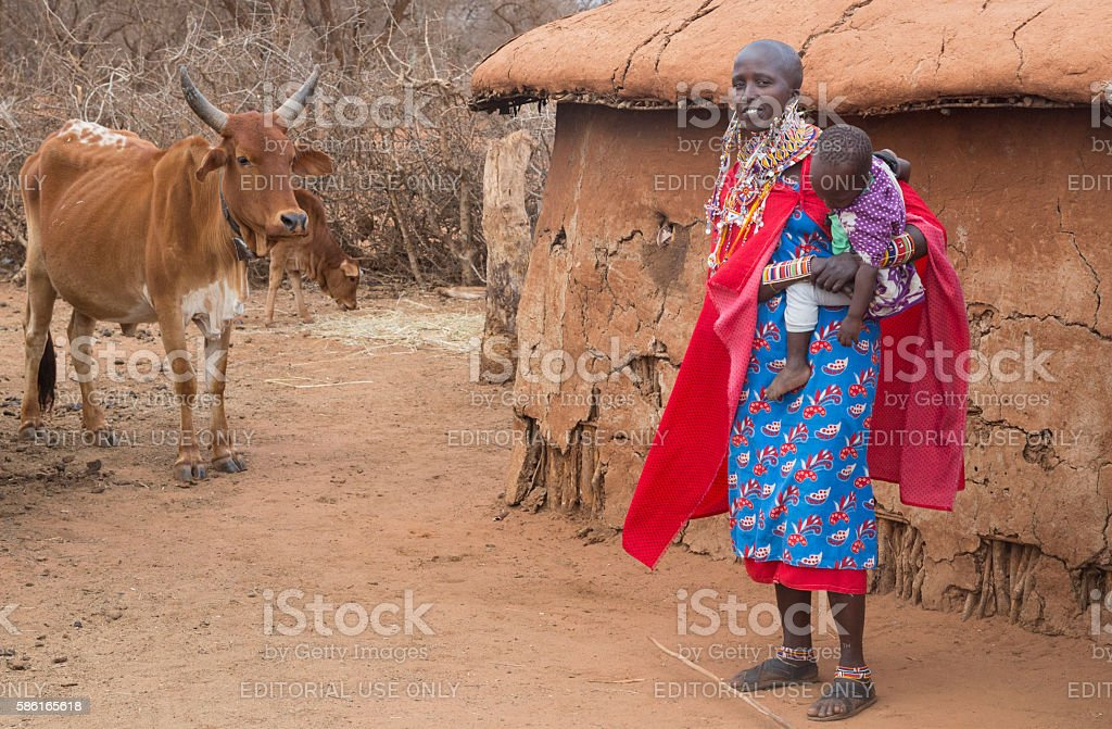 Maasai woman with child in front of hut, Kenya, stock photo