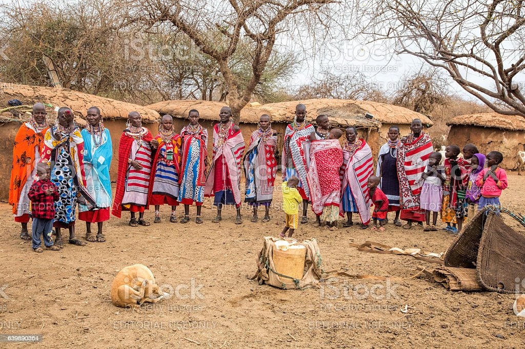Maasai women and children in front of huts stock photo