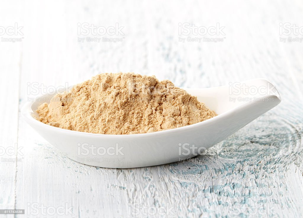 Maca powder in white porcelain spoon stock photo