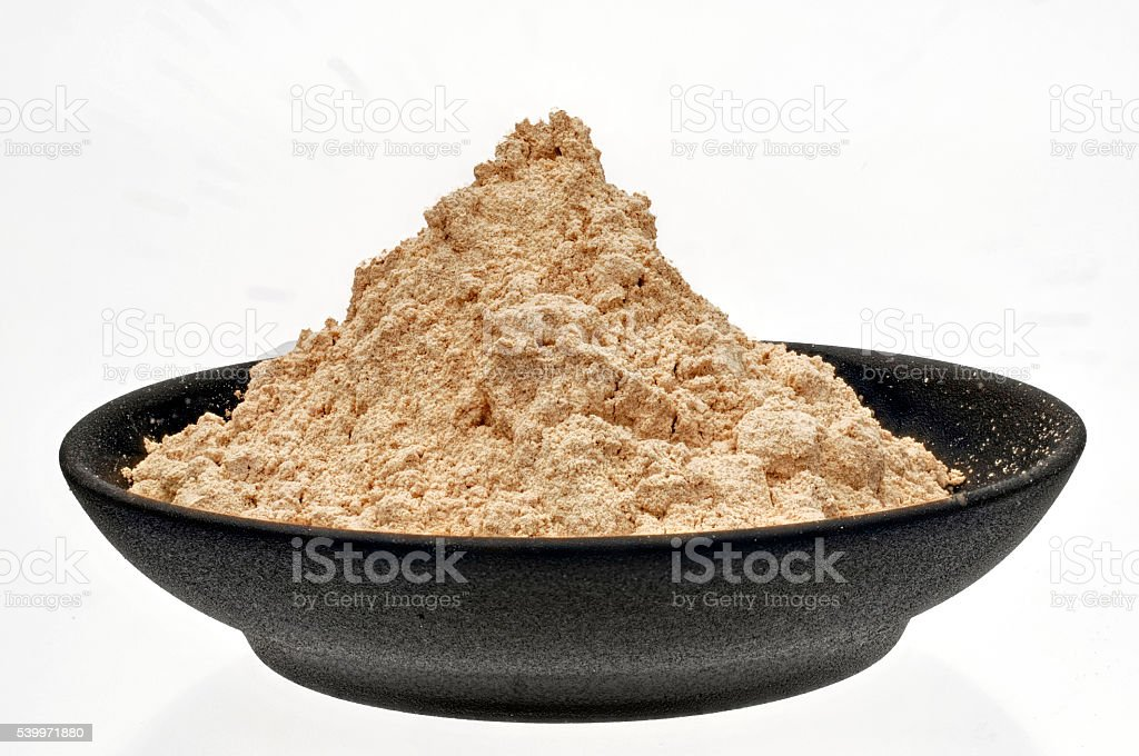 Maca powder Superfood in a black bowl stock photo