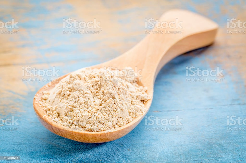 maca root powder on wooden spoon stock photo
