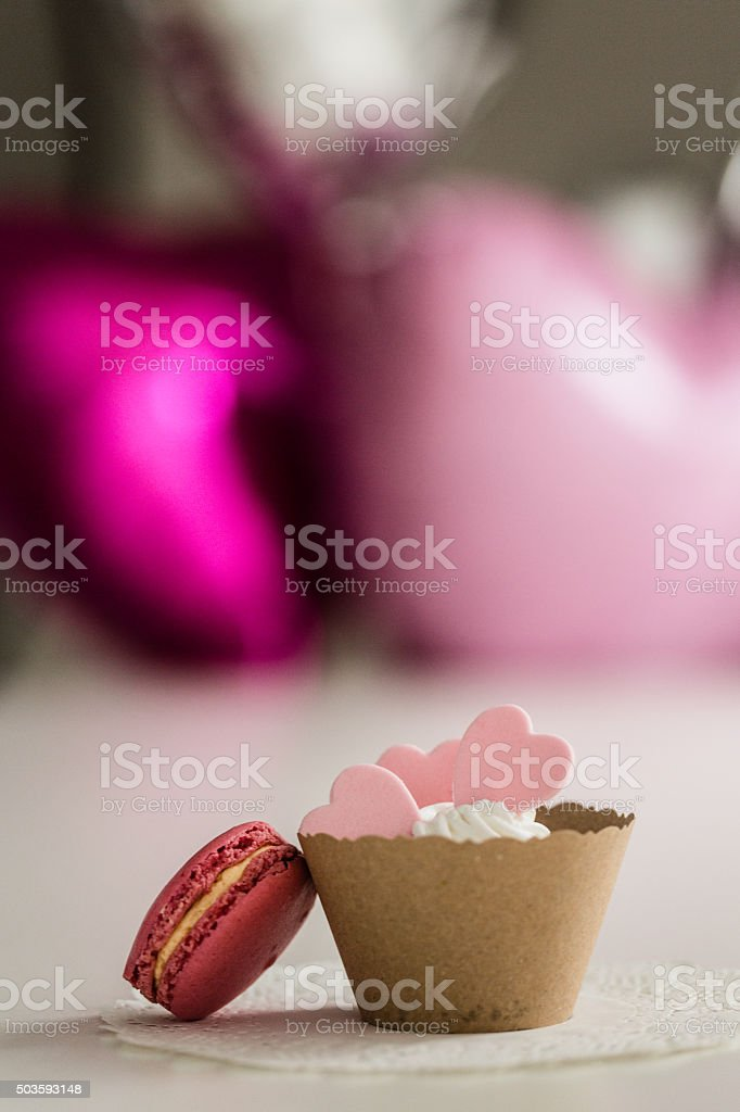 Macaron and cupcake with pink hearts stock photo