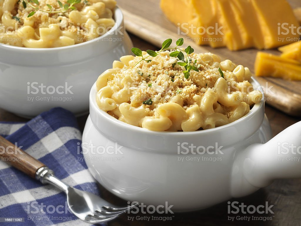 Macaroni and cheese in a white bowl on blue plaid tablecloth stock photo