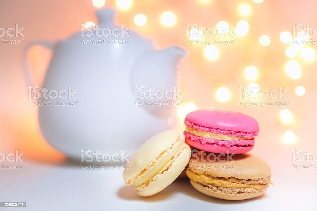 Macaroons and elegant tea pot on white table stock photo