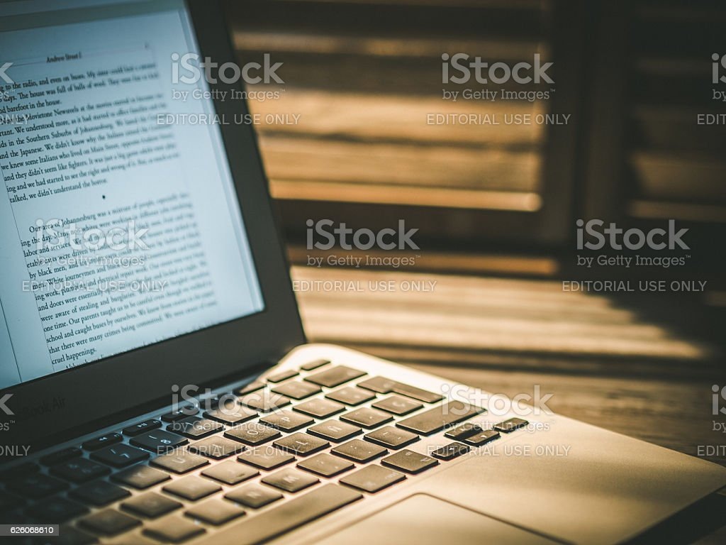 MacBook Air laptop beside wooden window with rays of light stock photo