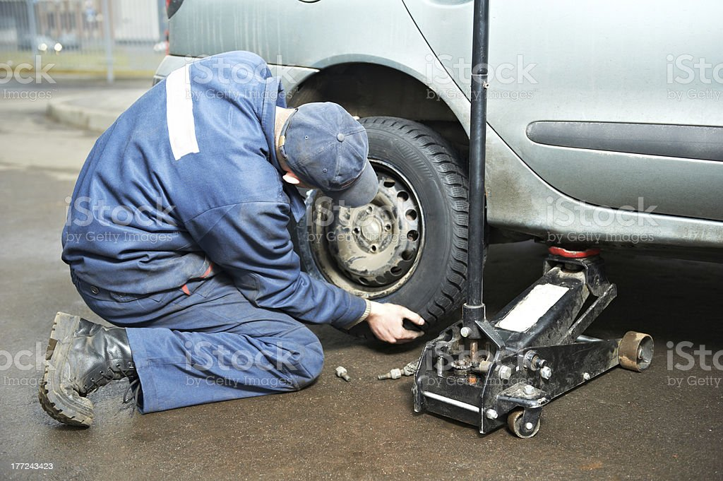 machanic repairman at tyre fitting with car jack royalty-free stock photo