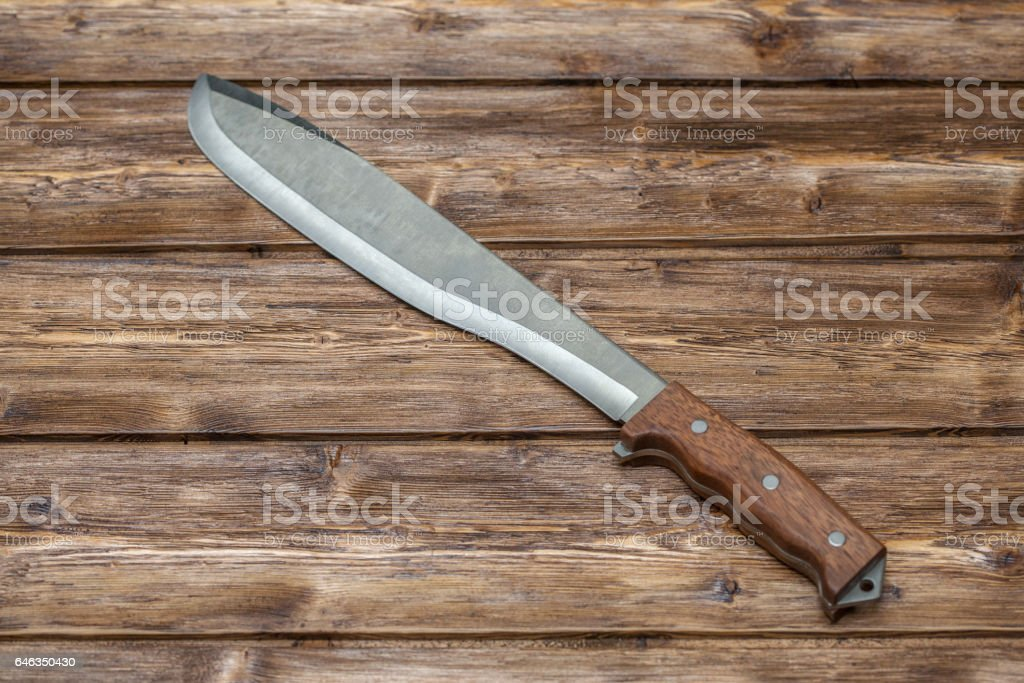 Machete for cutting grass on wooden background stock photo