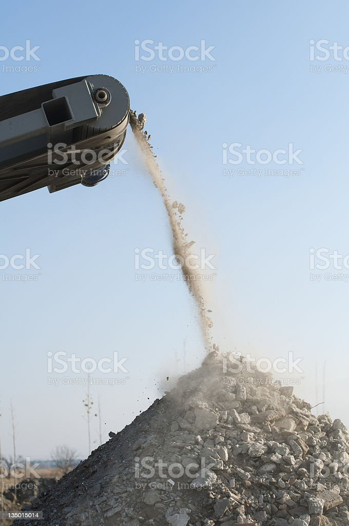 A machine crushing stone and dropping it into a pile stock photo