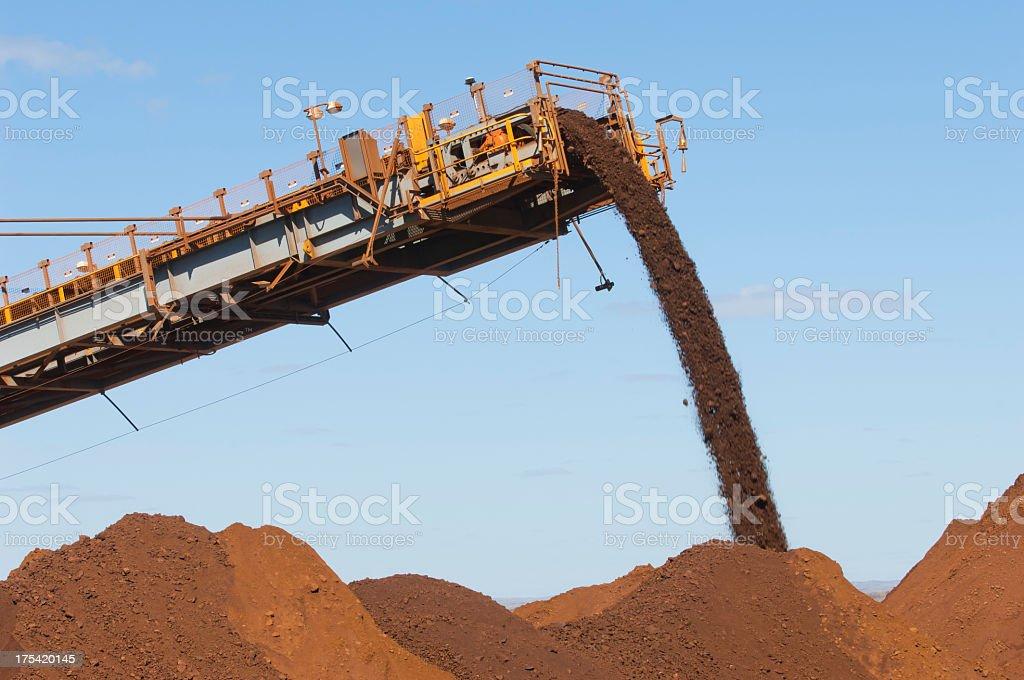 Machine dumping ore in stockpile stock photo
