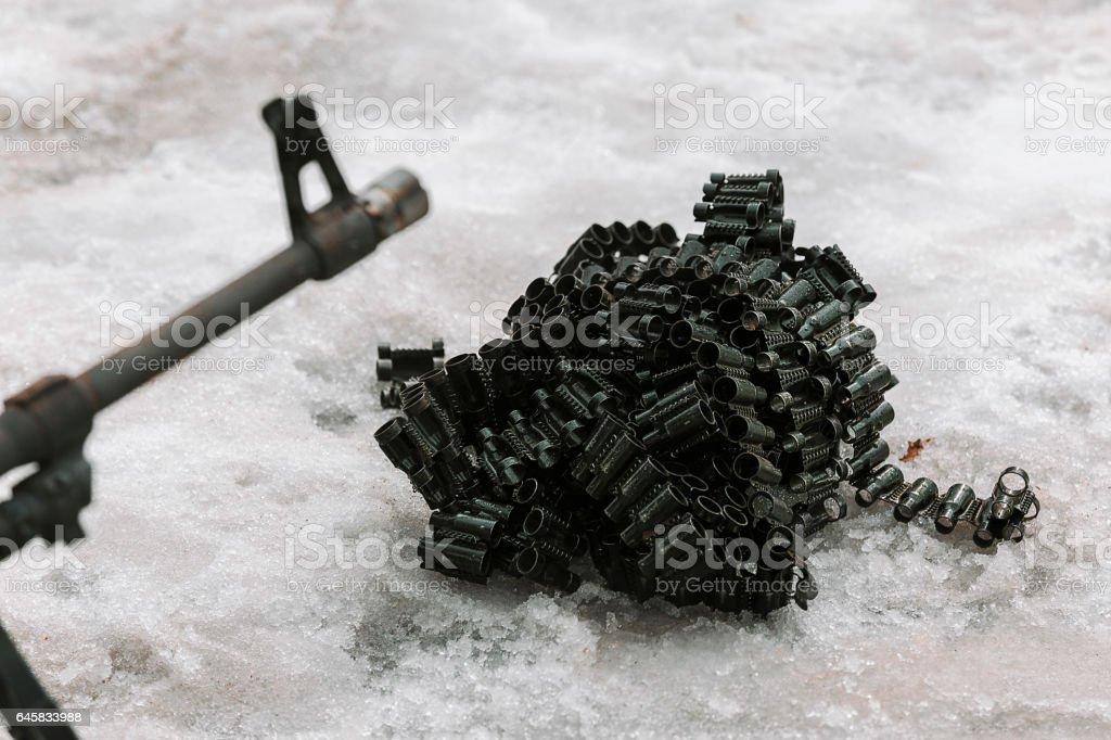 Machine gun with ammunition belts on snow stock photo