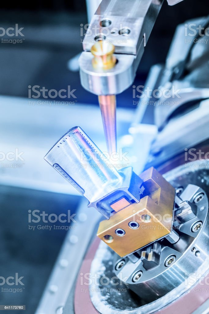 EDM machine handles aircraft engine turbine blade. stock photo